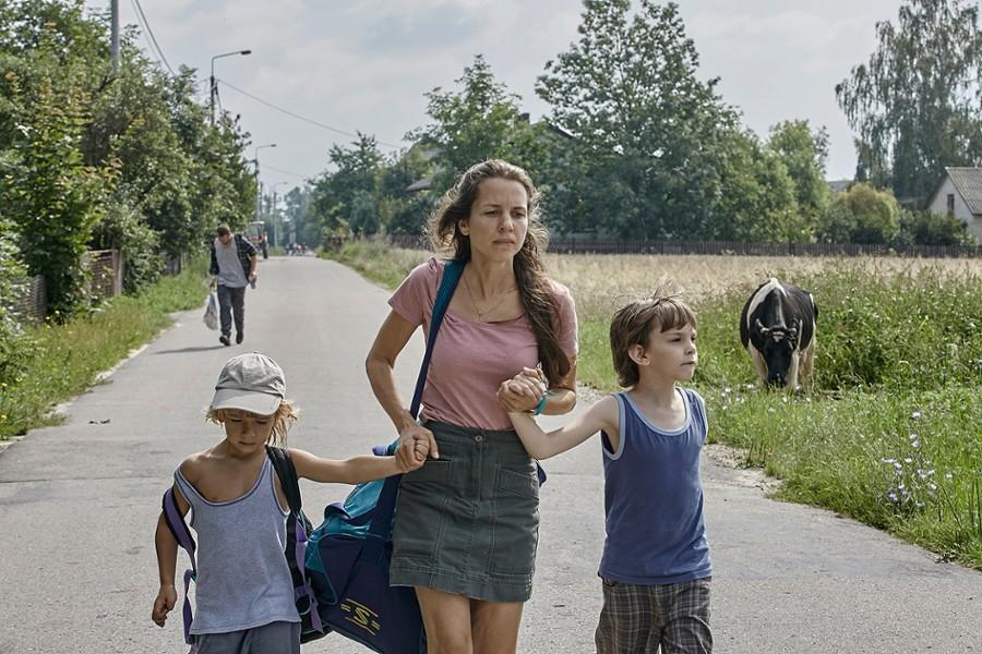 kobieta biegnącą z dwójką dzieci za rękę na asfaltowej alejce wśród terenów zielonych