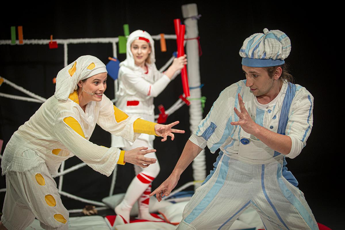 aktorzy w białych kostiumach występują w spektaklu