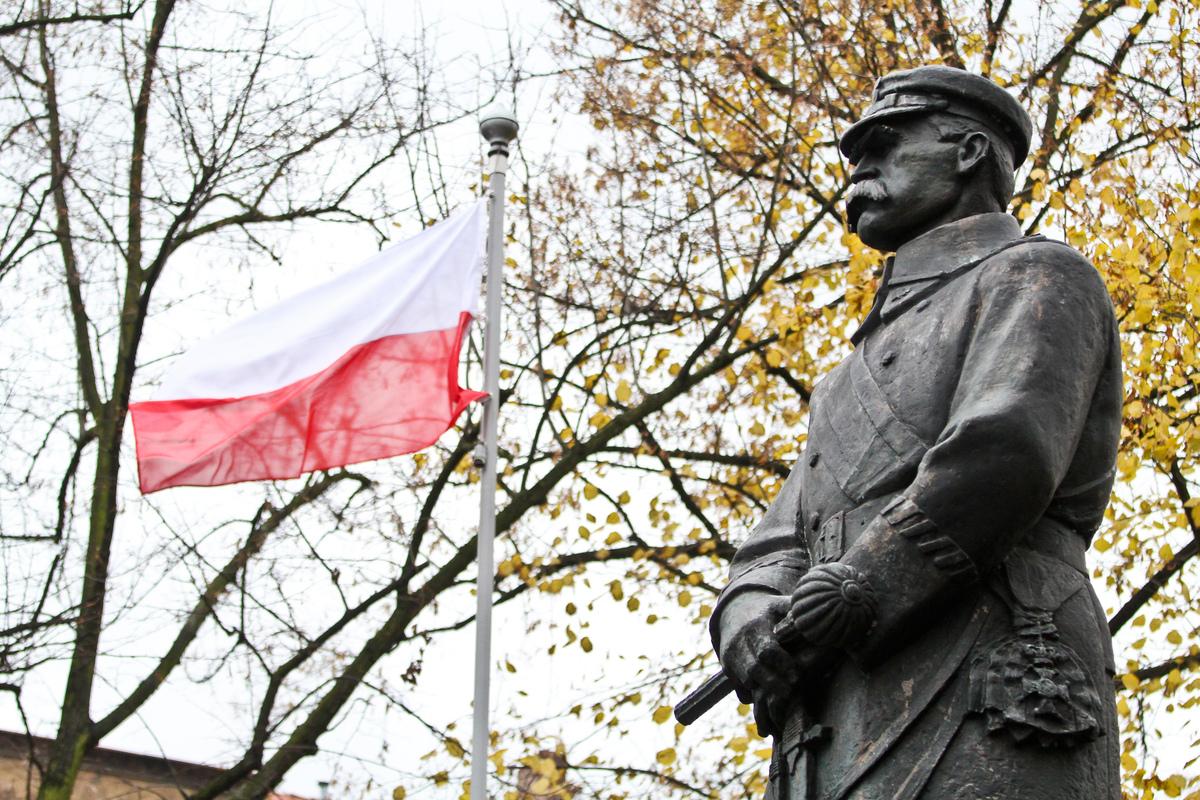 pomnik marszałka Piłsudkiego z flagą Polski w tle