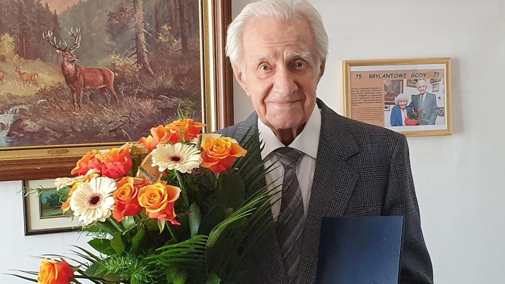 pan Władysław w garniturze, z bukietem kwiatów