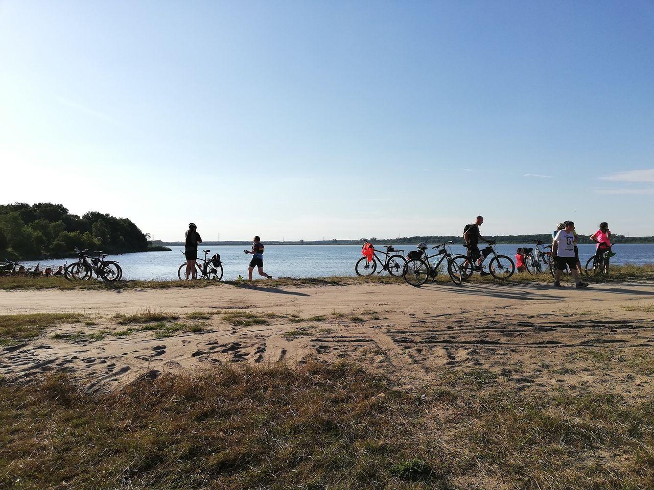ludzie na rowerach nad wodą