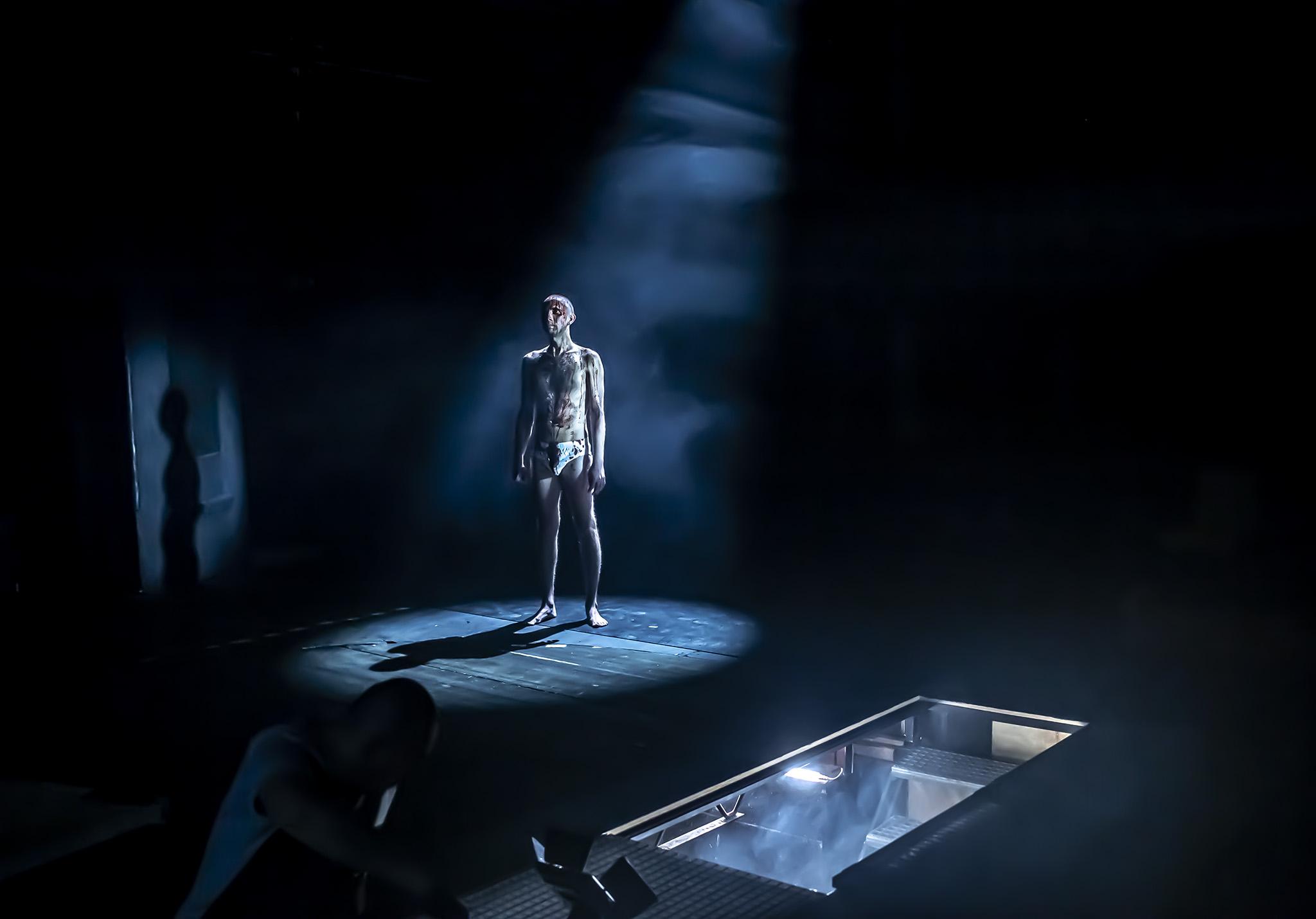 aktor na scenie, ucharakteryzowany, rozebrany do bielizny i pomazany krwią