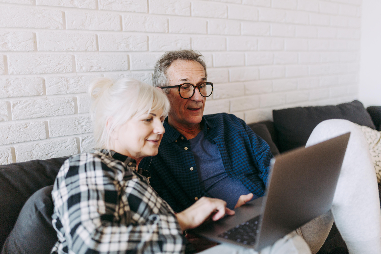 starsi luidzie siedzą na kanapie przy laptopie