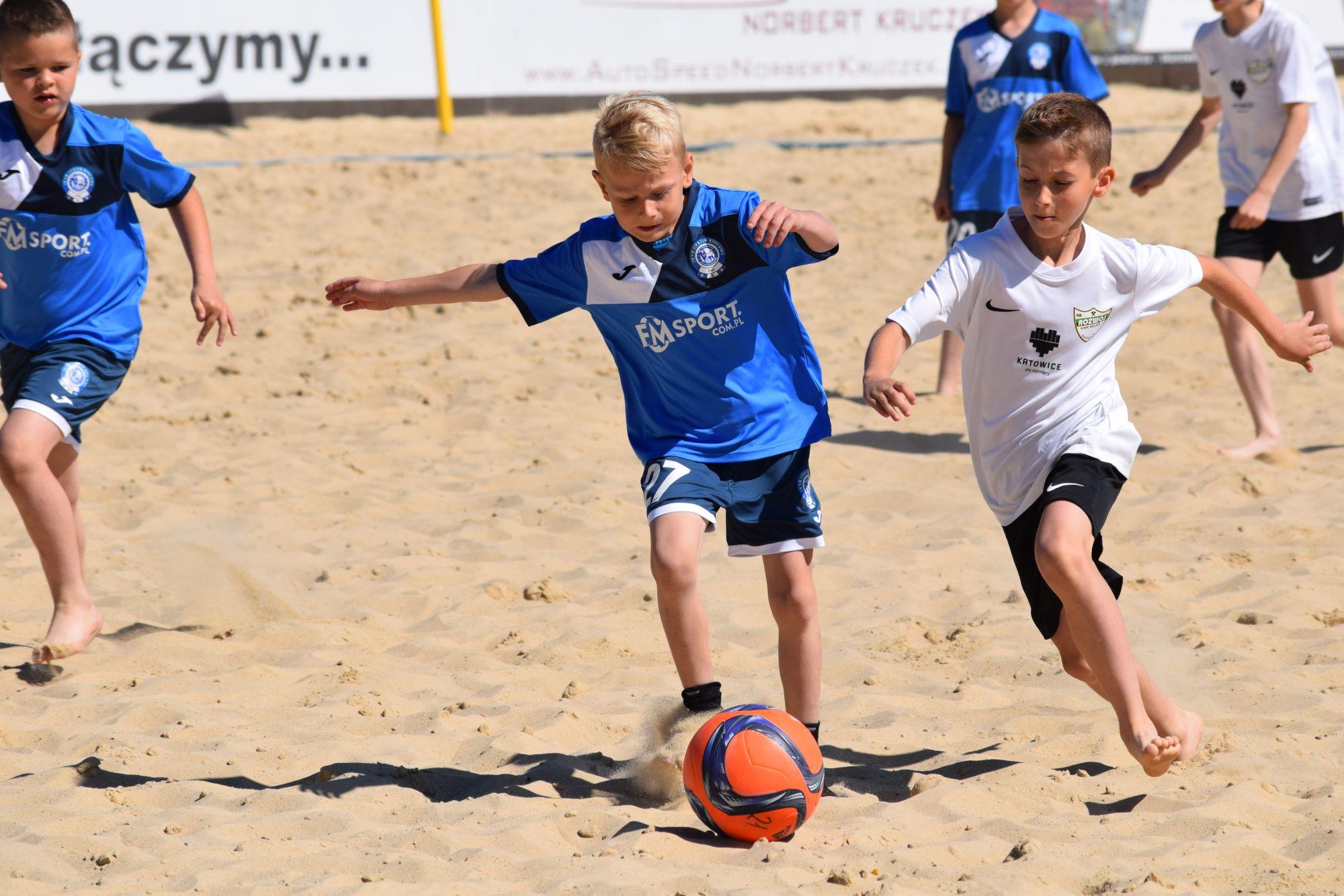 dzieci grają w piłkę nożną plażową