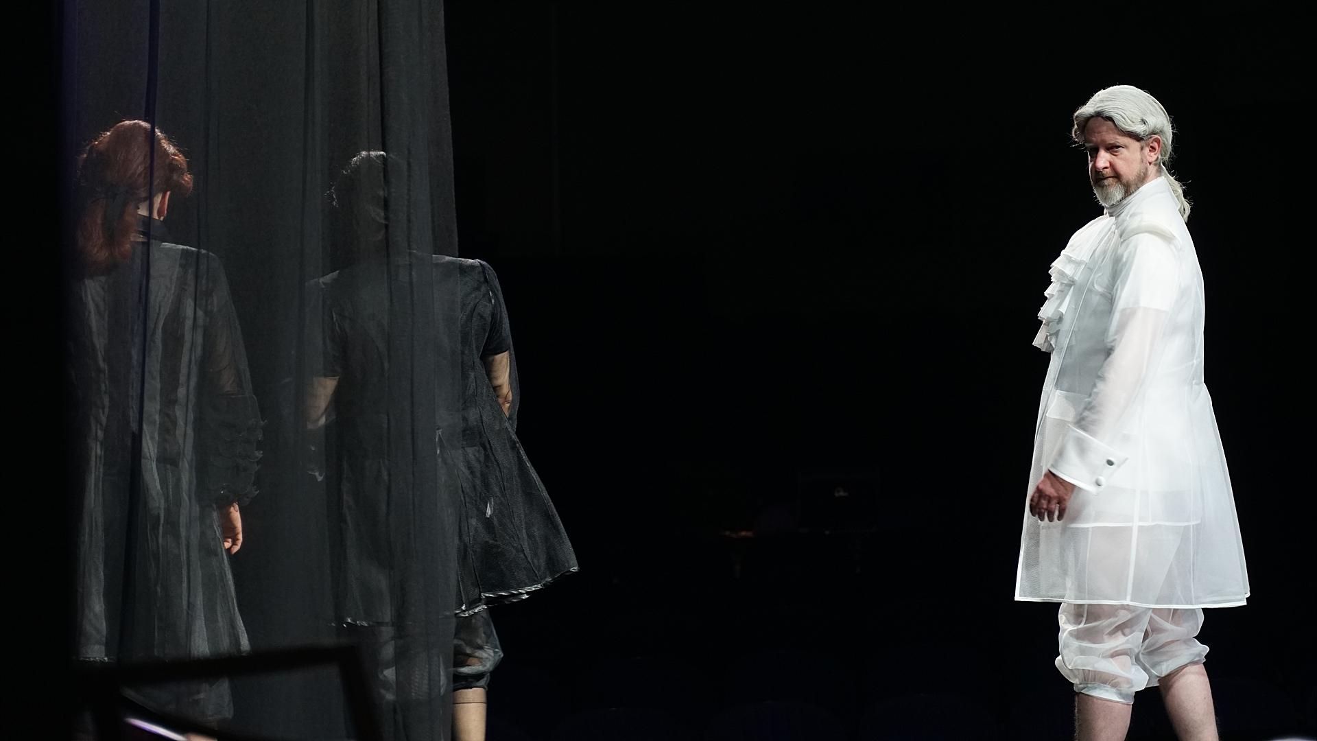 mężczyzna w białych pantalonach i kostiumie na czarnym tle, dwie odwrócone tyłem postaci na dalszym planie