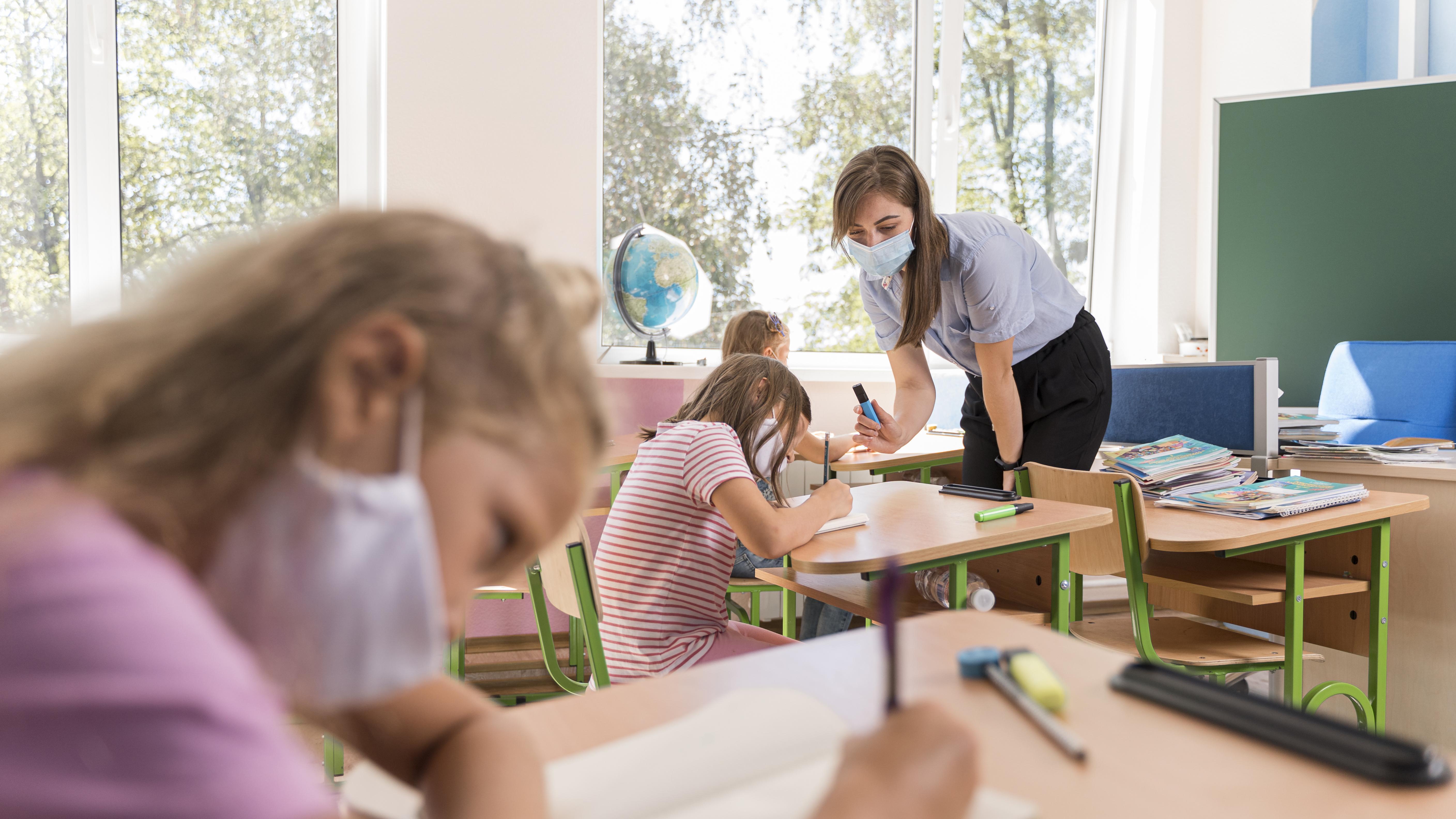 uczniowie i nauczycielka w maseczkach