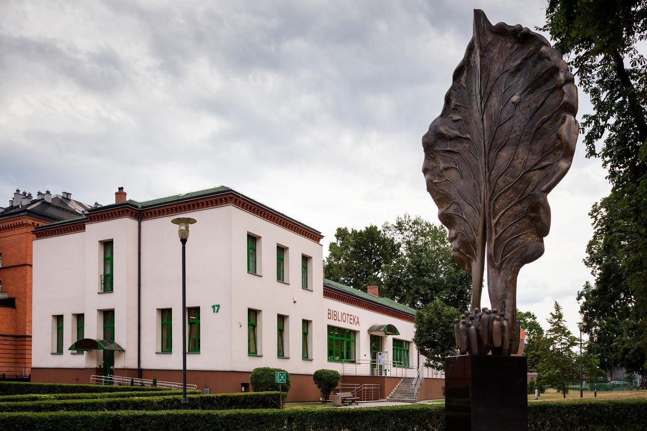 na pierwszym planie rzeźba liścia, w tle biblioteka główna