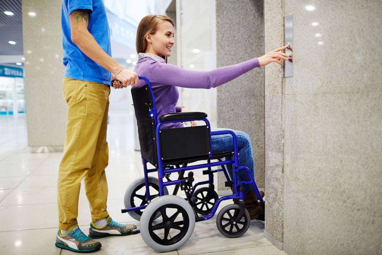kobieta na wózku inwalidzkim korzysta z windy z osobą towarzyszącą