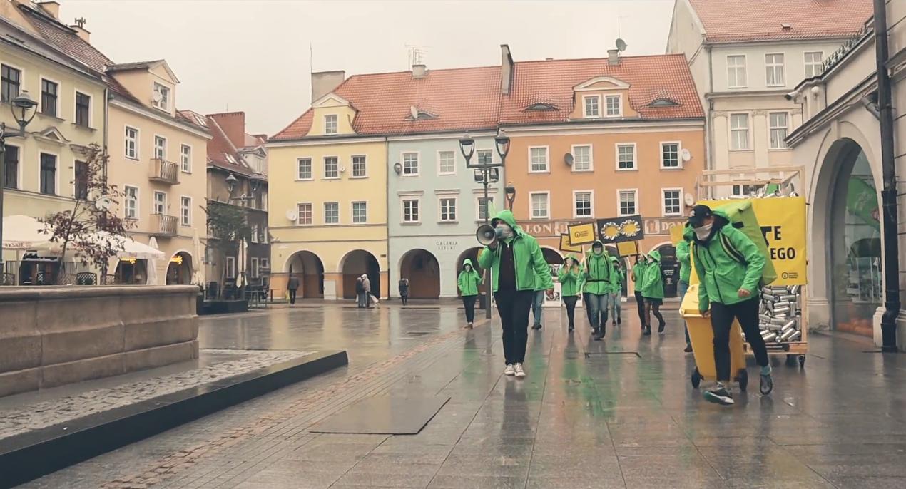 grupa ubranych na zielono aktywistów z instalacją z aluminiowych puszke przy Ratuszu