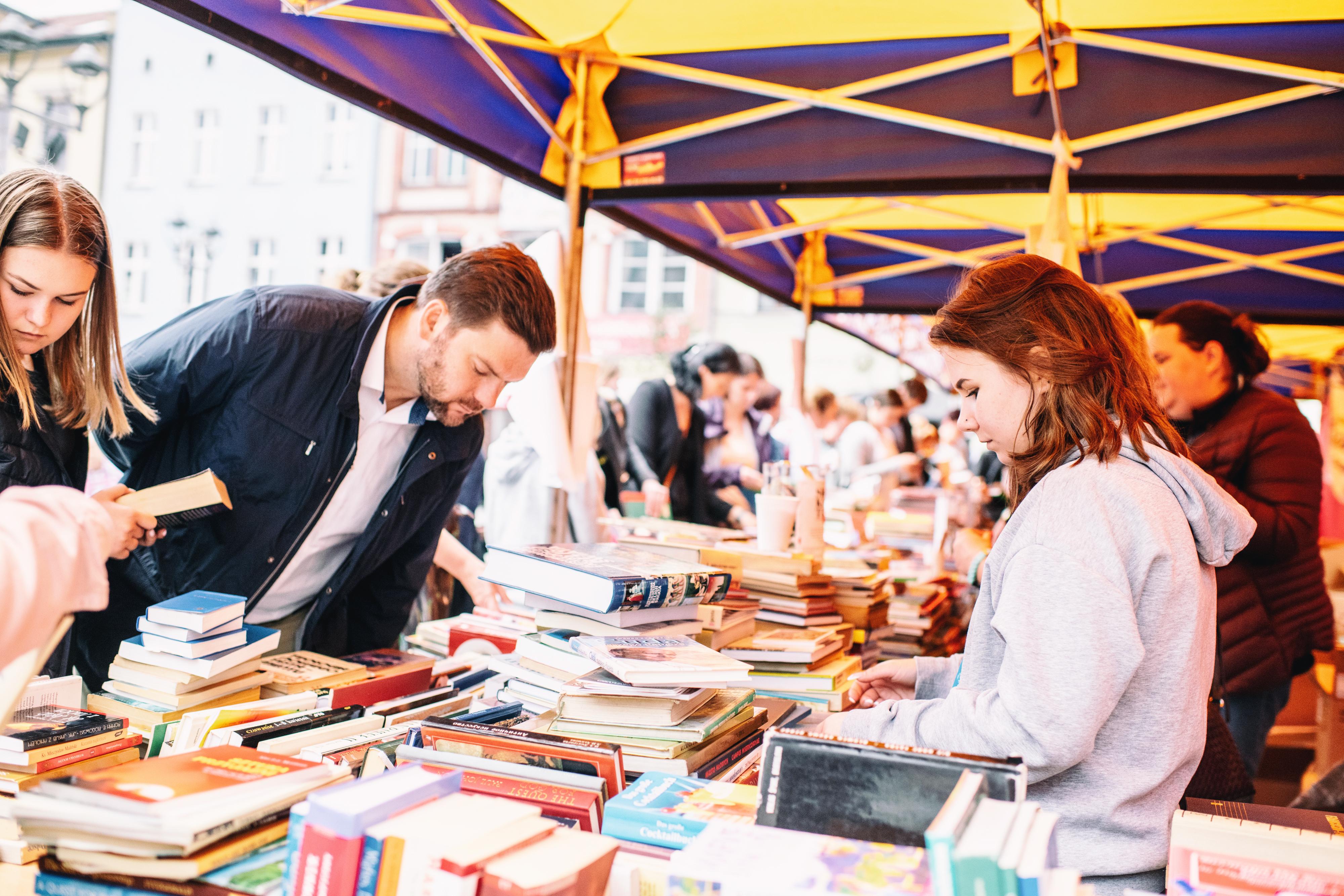 ludzie przeglądający książki na stoisku pod namiotem