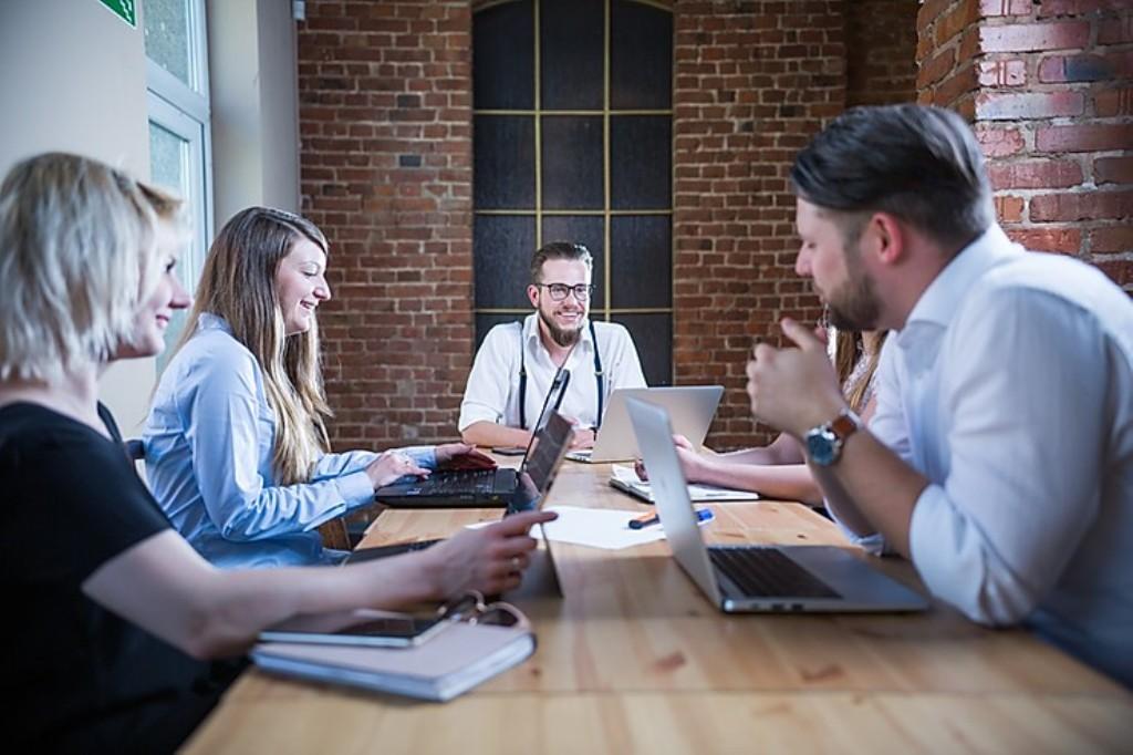 grupa młoldych ludzi rozmawia przy stole