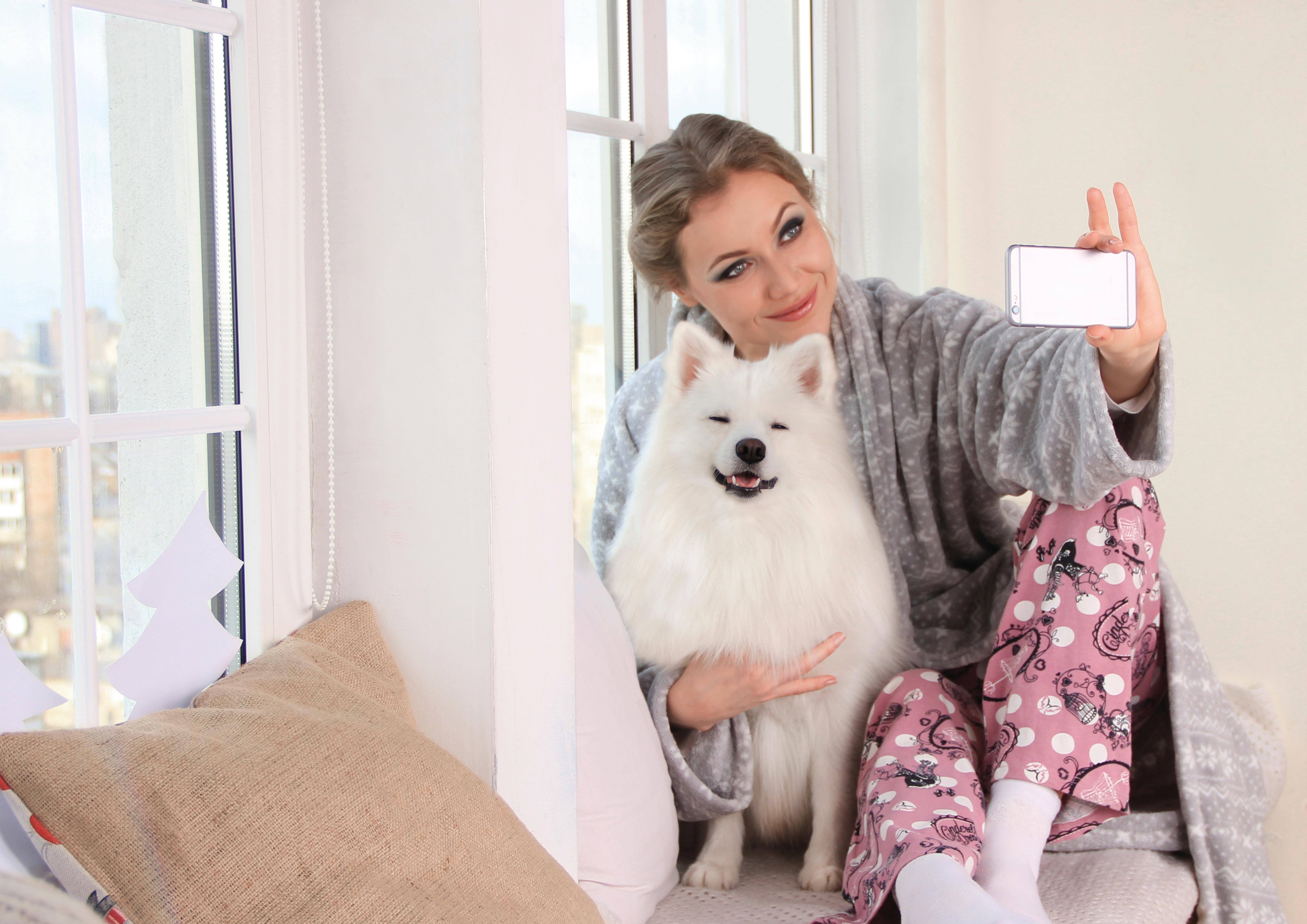 dziewczyny w piżamie z psem, robi selfie przy oknie mieszkania