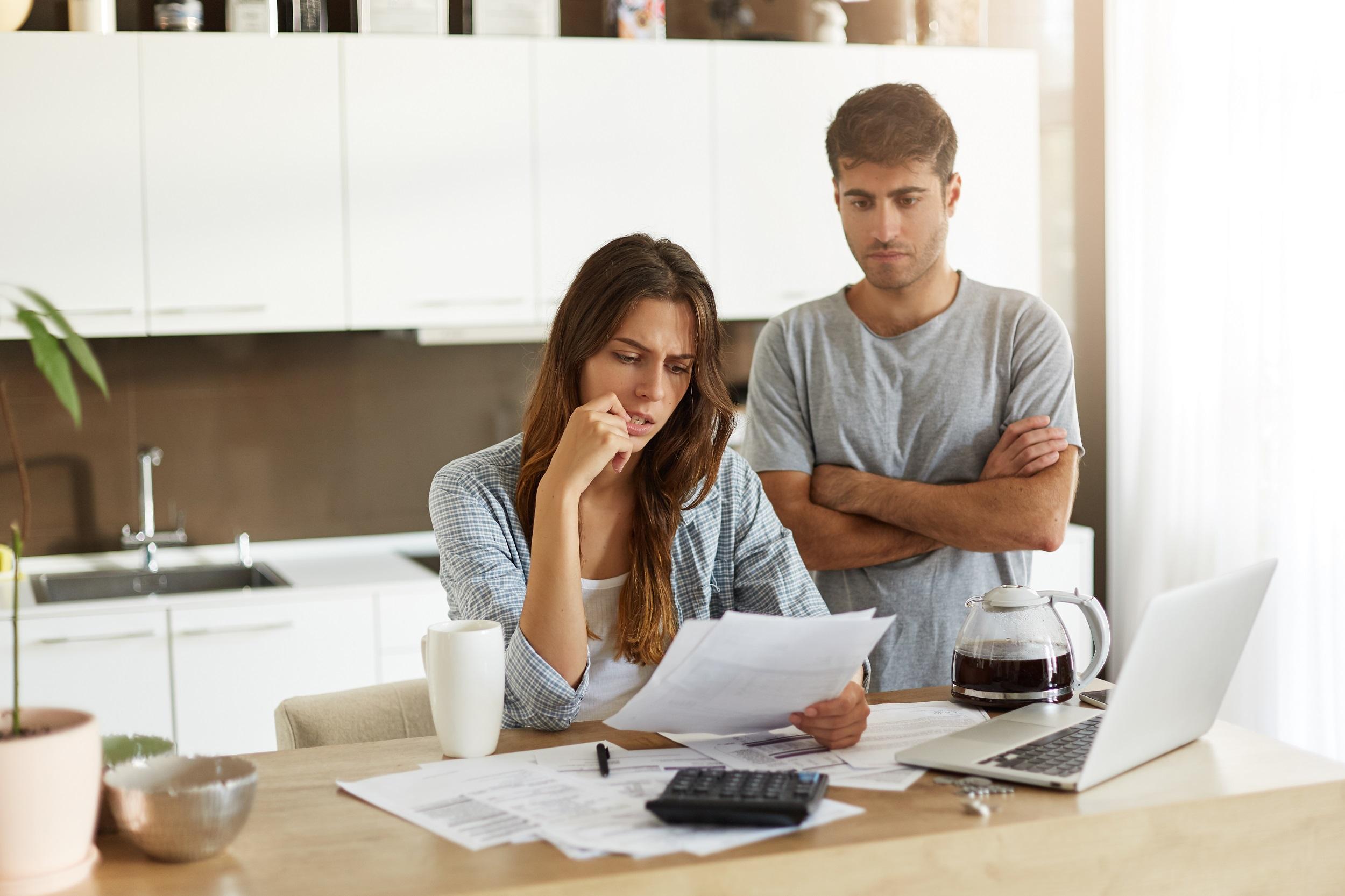 kobieta i mężczyzna liczący rachunki pzy stole