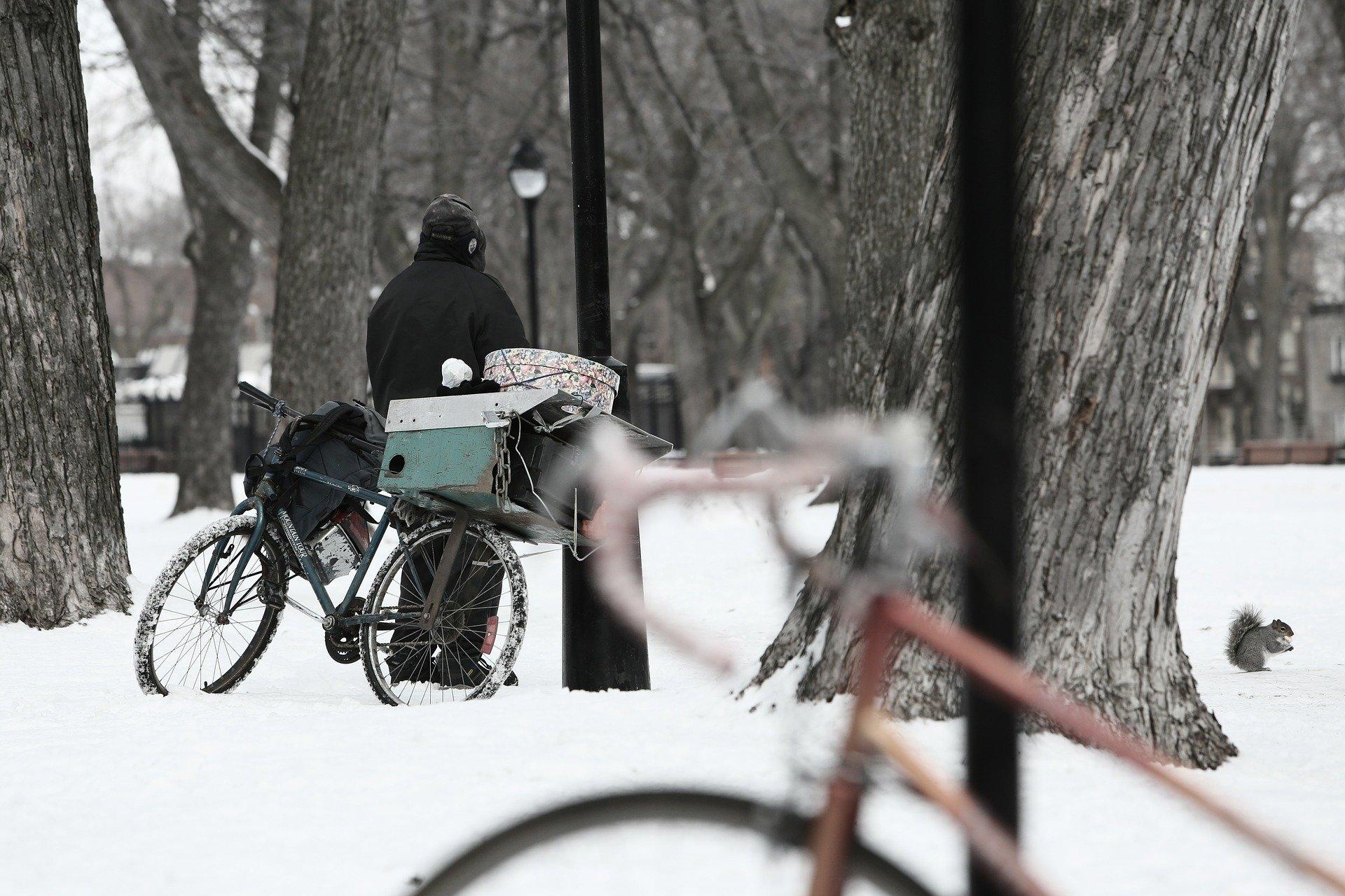 człowiek w oddali na śniegu, przy rowerze