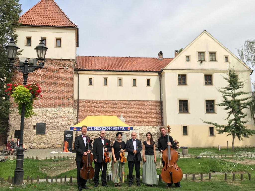 grupa eleganckich muzyków na trawniku przed Zamkiem Piastowskim