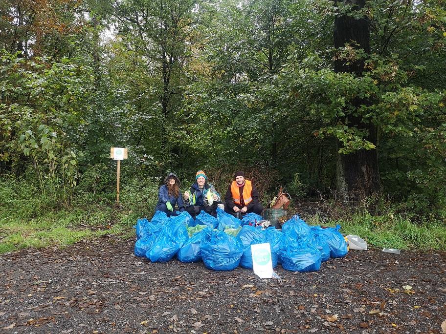 ludzie z workami śmieci w lesie