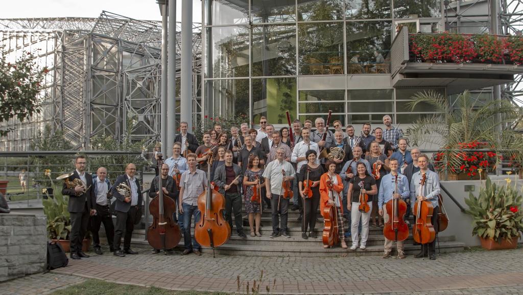 muzycy orkiestry stoją z instrumentami na schodach przed palmiarną