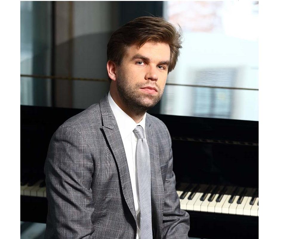 mężczyzna w garniturze, w tle fortepian