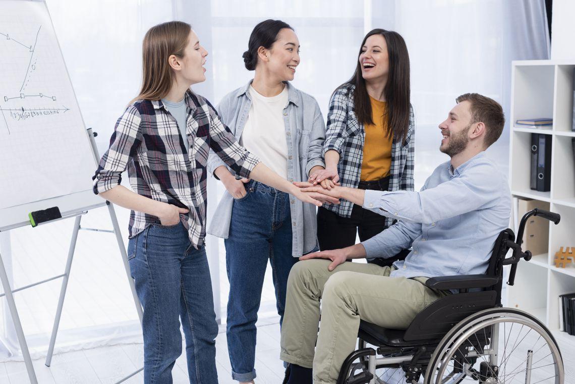 zespół pracowników,w tym osoba na wózku inwalidzkim
