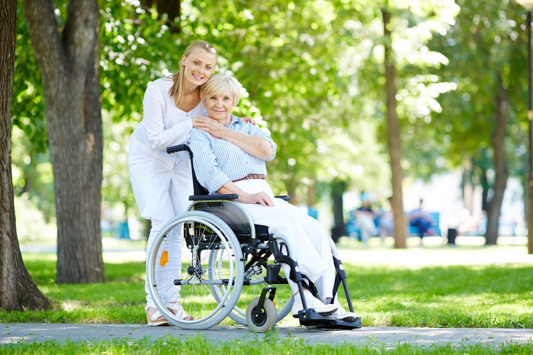 młoda kobieta przytula starszą kobietę siedzącą na wózku inwalidzkim