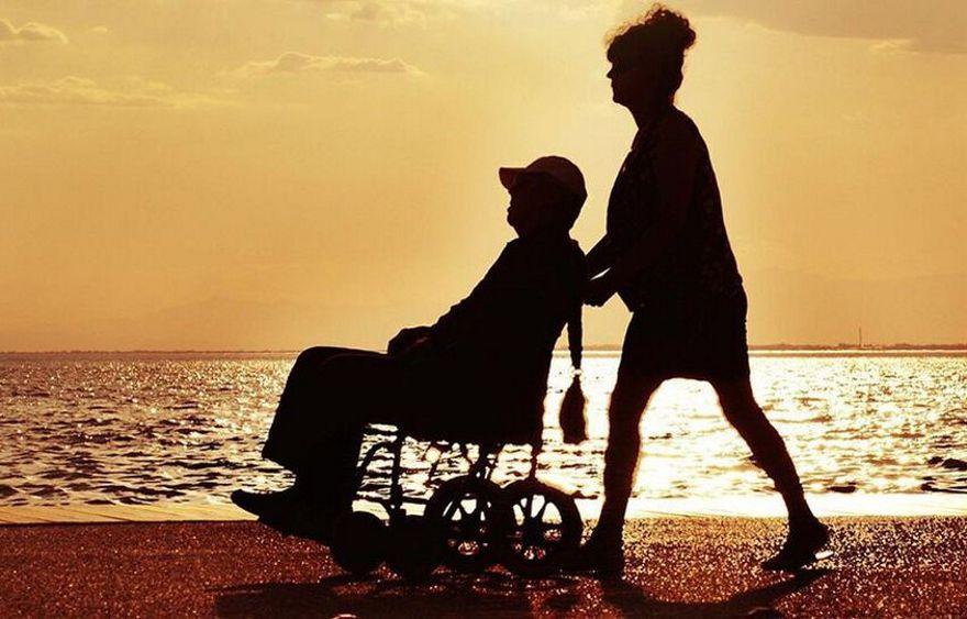 kobieta pcha po plaży wózek iwalidzki z siedzącym mężczyzną