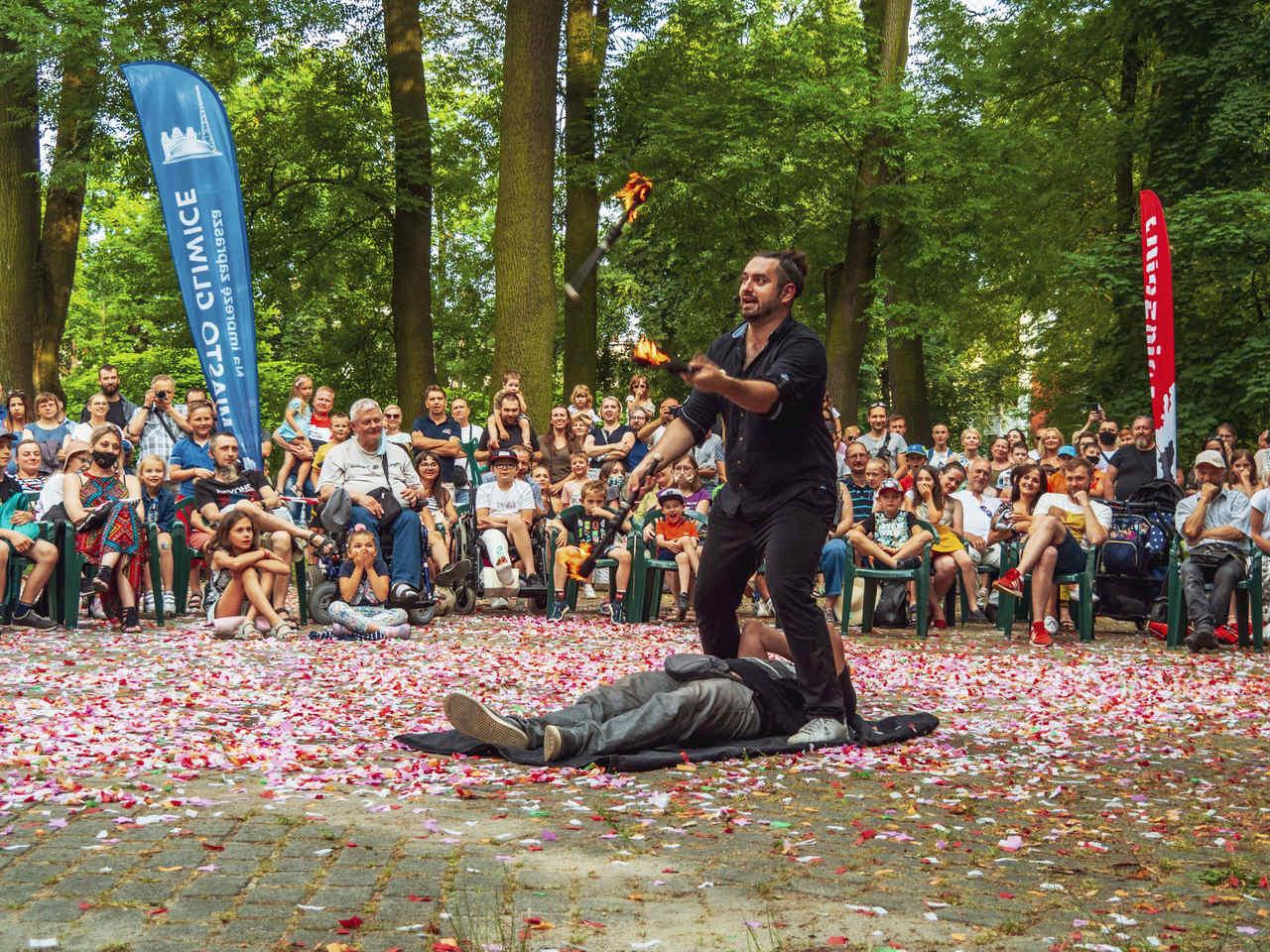 występ akrobatyczny, wokół artystów publiczność w parku