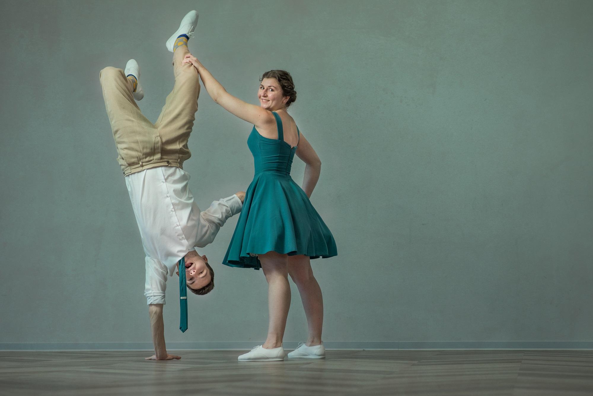 chłopak stoi na rękach, dziewczyna trzyma jego nogę