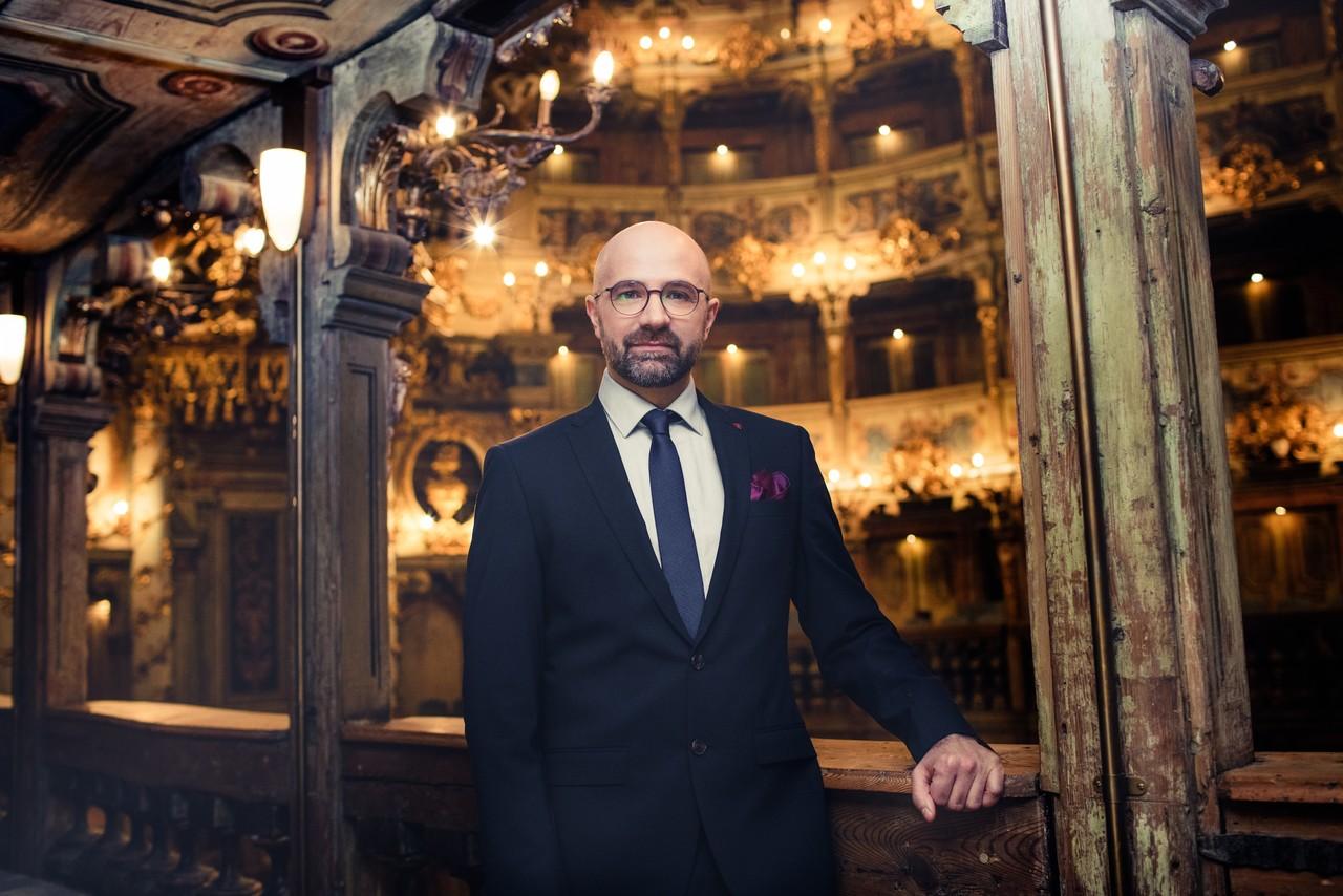 mężczyzna w teatrze, elgancko ubrany, w okularach, między kolumnami na balkonie