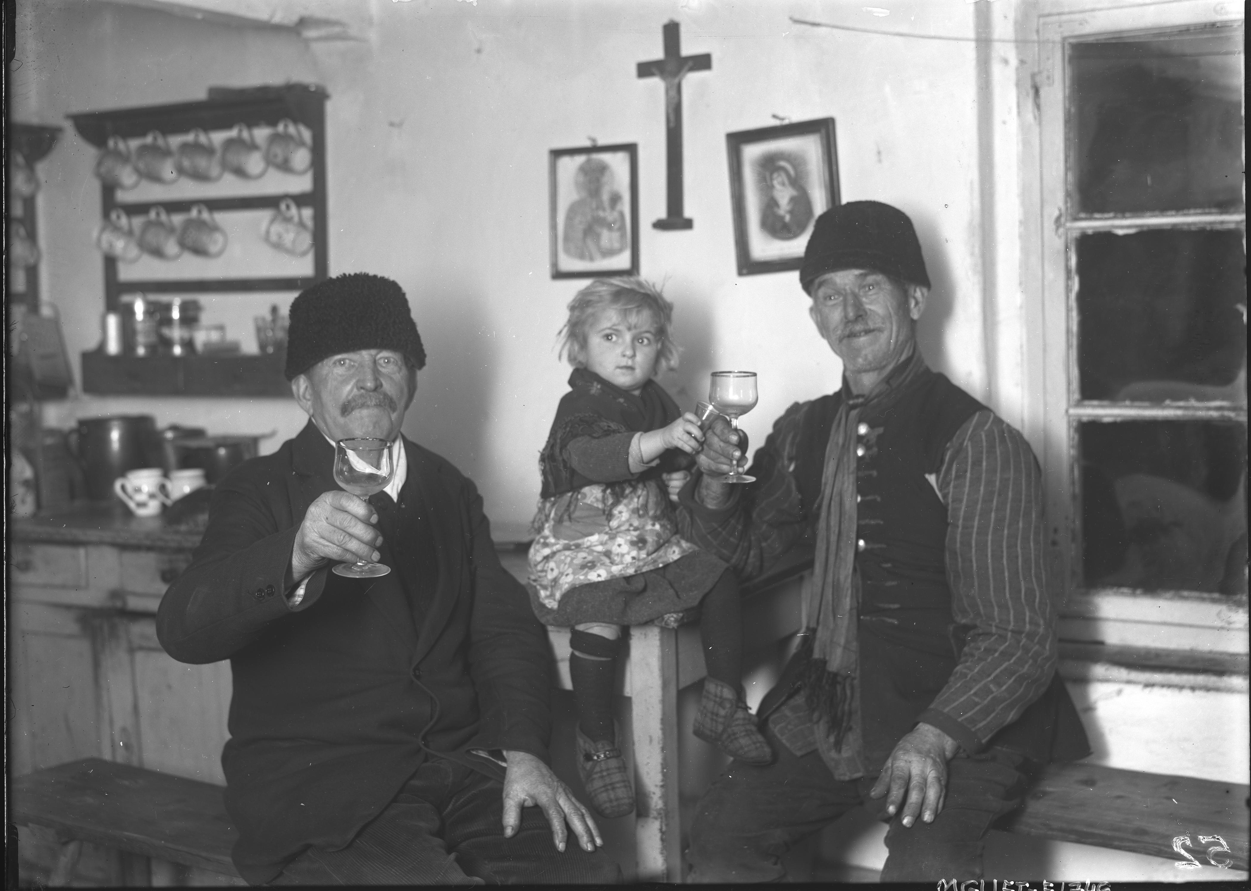 dwóch mężczyzn trzzymających kieliszki i dziecko na rękach