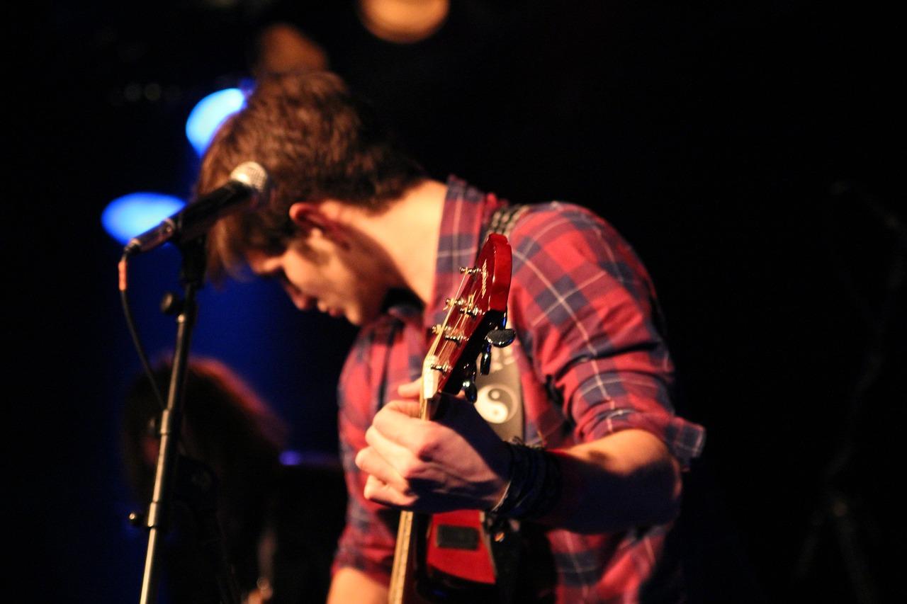 chłopak z gitarą przy mikrofonie