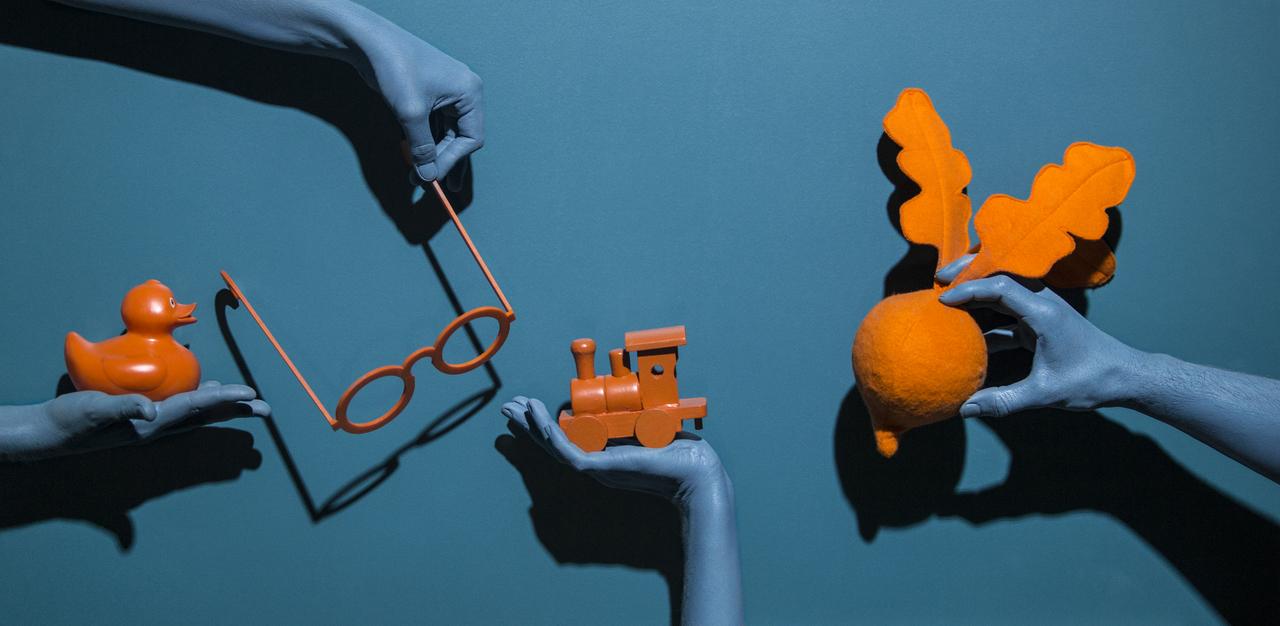 zdjęcie wyciągniętych rąk z pomarańczowymi obiektami