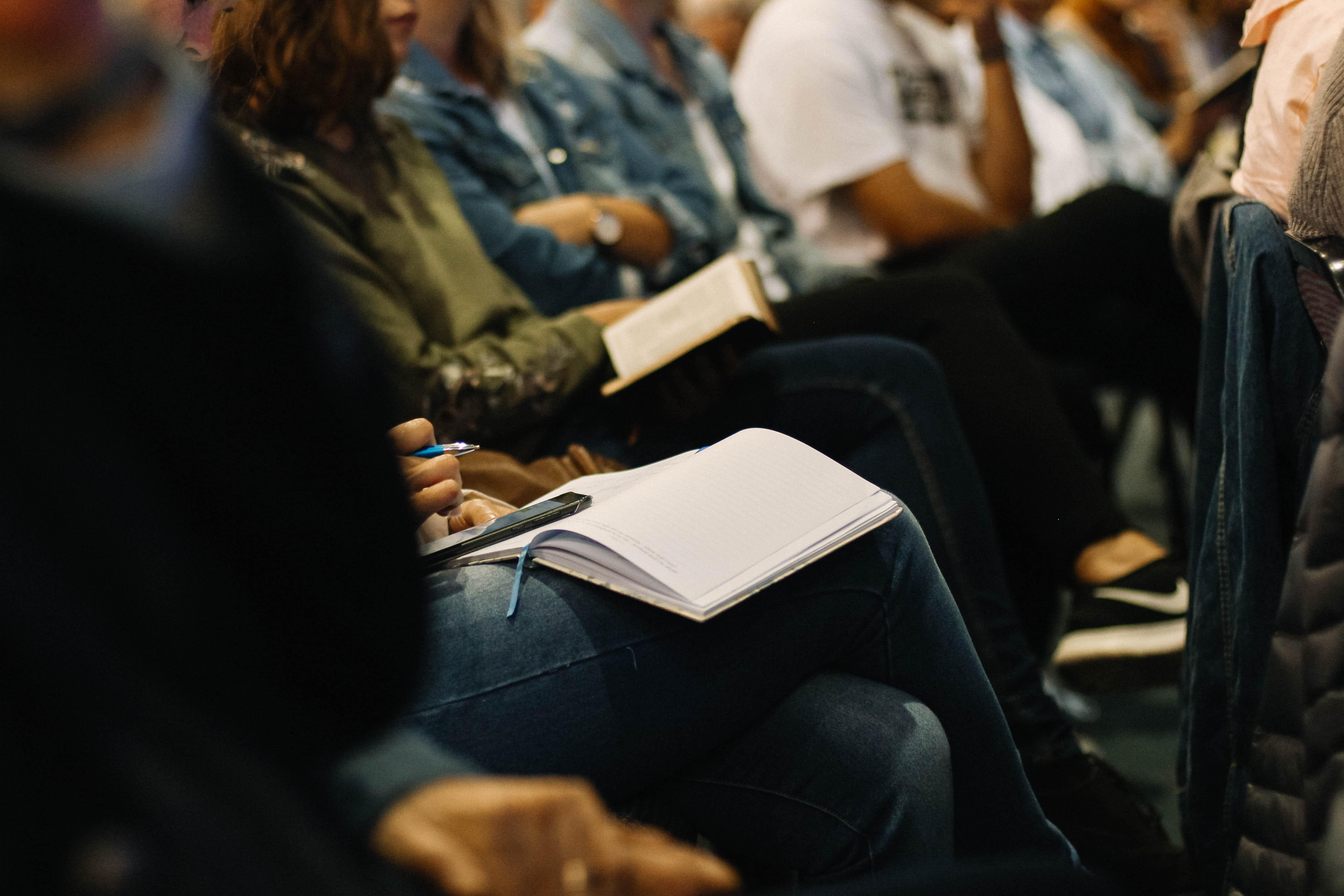 ludzie siedzący na krzesłach z notatkami