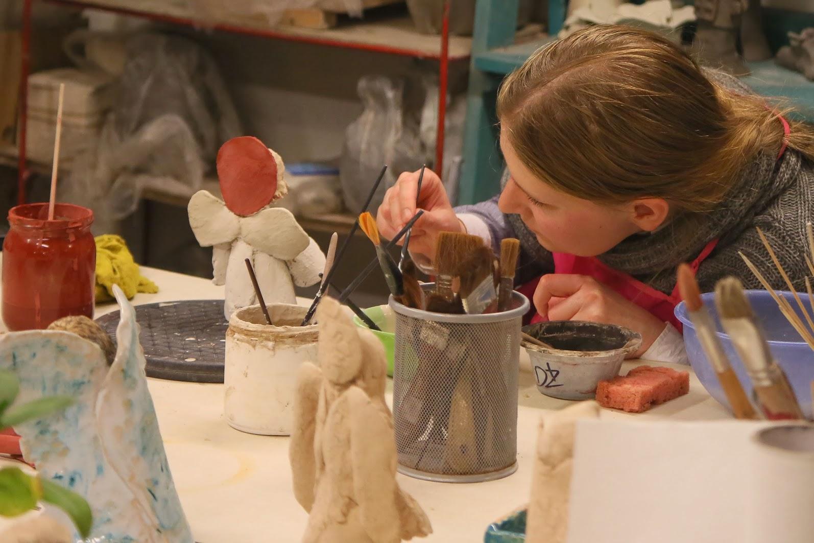 kobieta maluje ceramiczne rzeźby