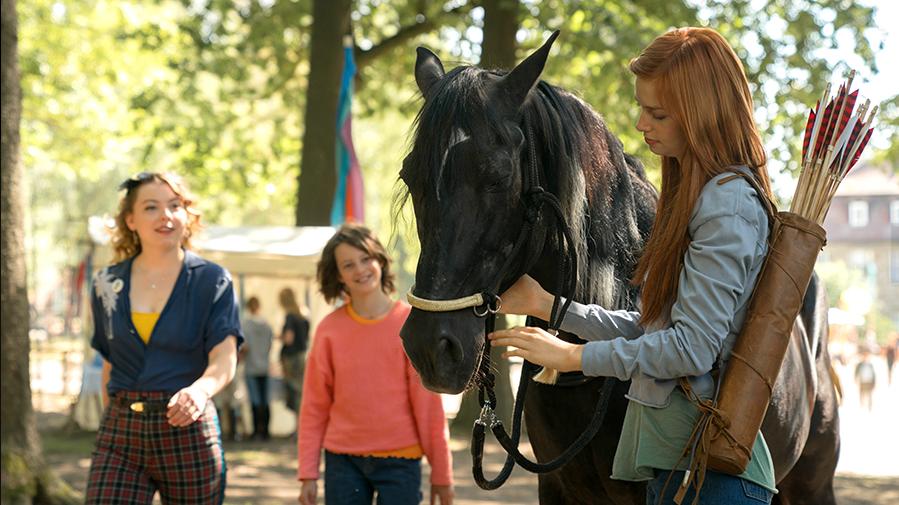 dziewczynka z koniem, na drugim planie dwie idąca kobiety