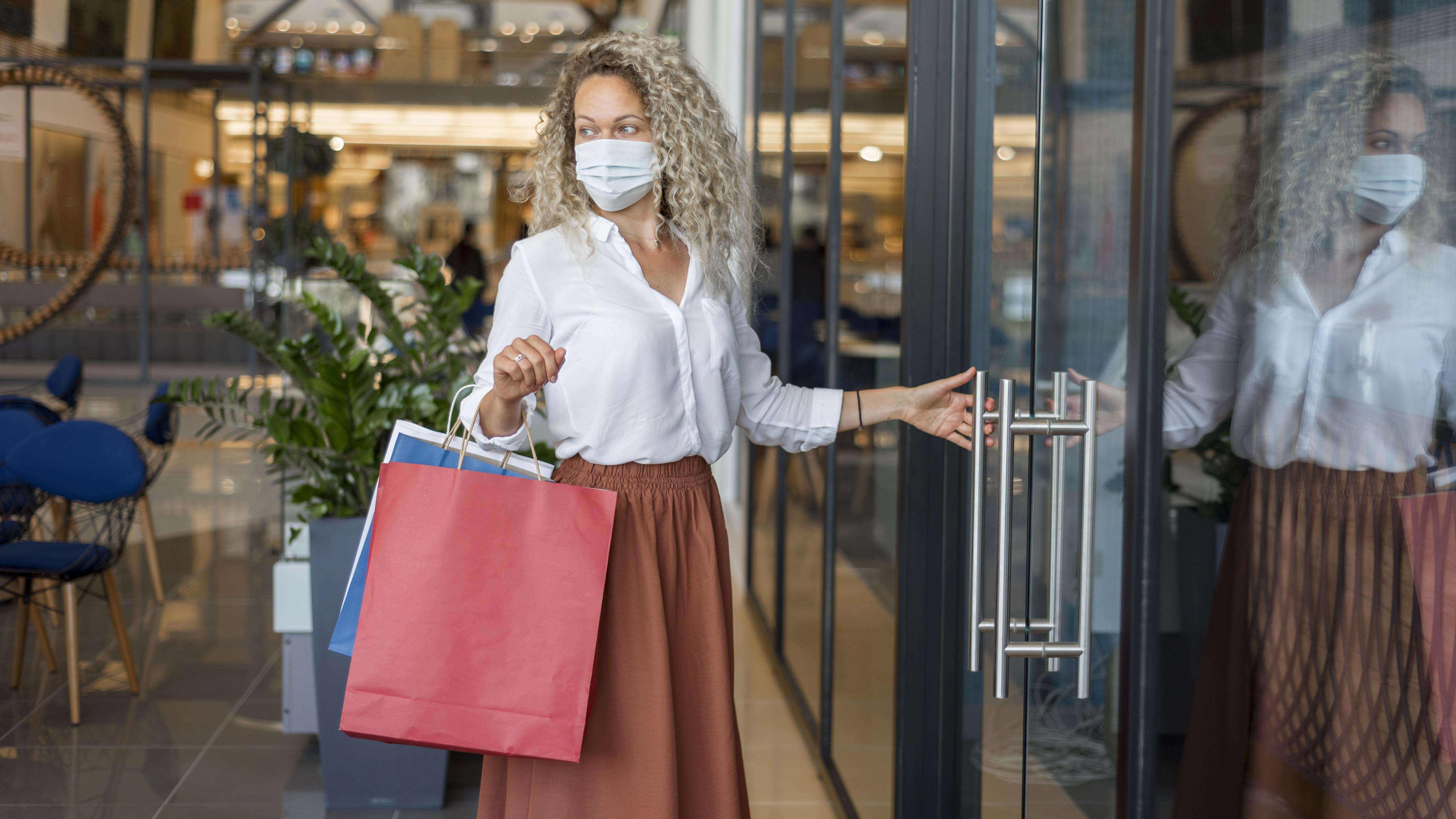 kobieta w maseczce wchodzi do sklepu w galerii handlowej