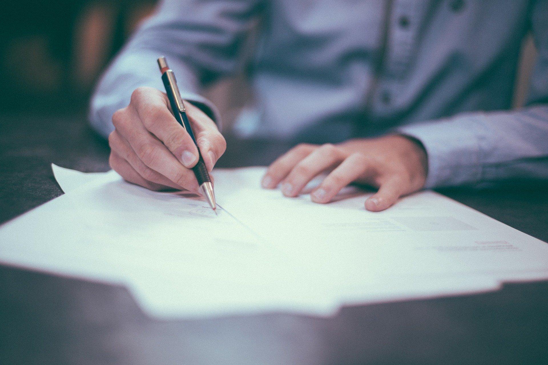 mężczyzna piszący na piórem na kartce papieru
