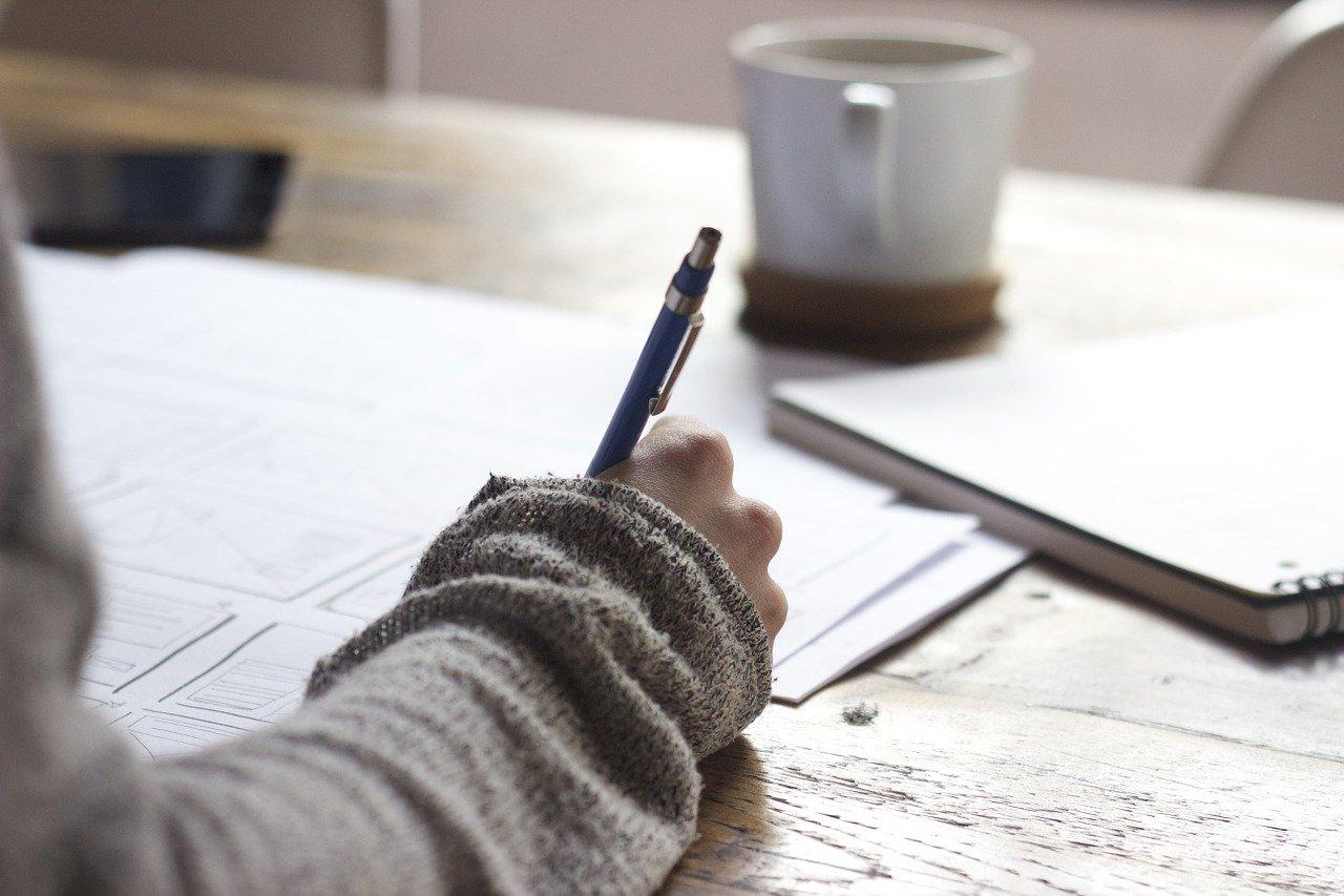 ręka z długopisem wypełniająca dokumenty