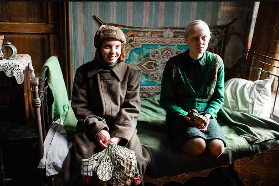 dwie kobiety siedzą na łózku i rozmawiają