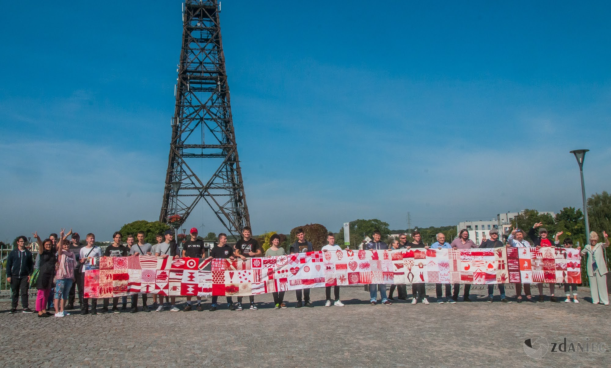 rozwinięta biało-czerwono-biała flaga pod Radiostacją i kilkudziesięciu uczestników, którzy ją trzymają