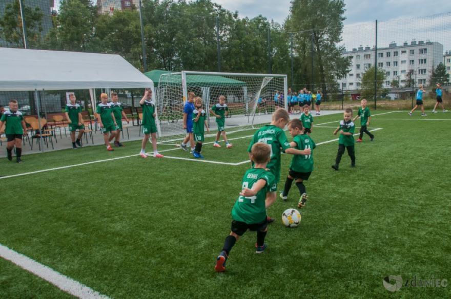 dzieci grają w piłkę nożną na boisku przyszkolnym