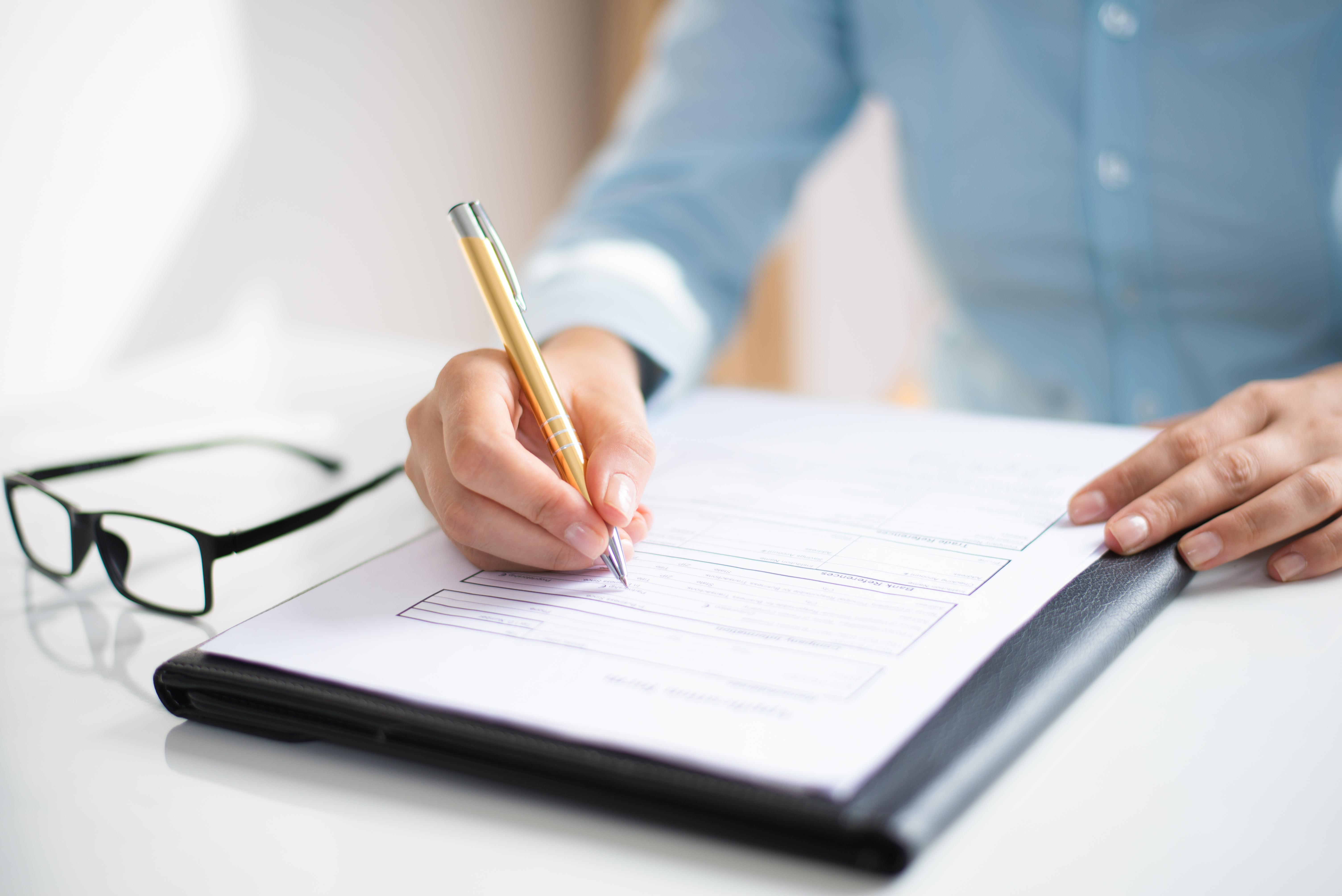 człowiek piszący na papierze