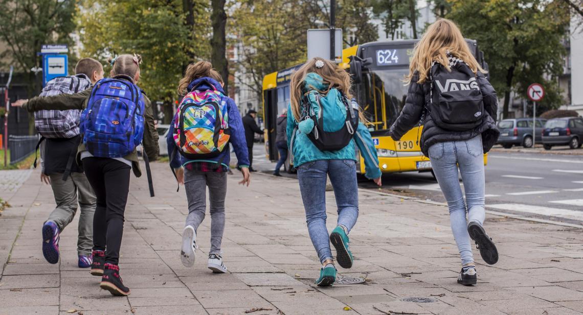 dzieci biegnące do autobusu